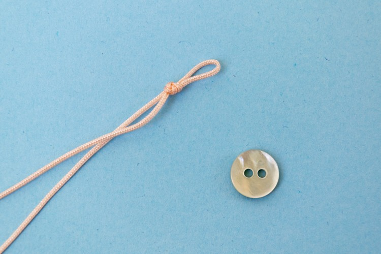 Make a loop in the cord that just fits your button