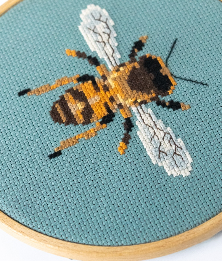 Close up of beginner cross stitch project amber bee